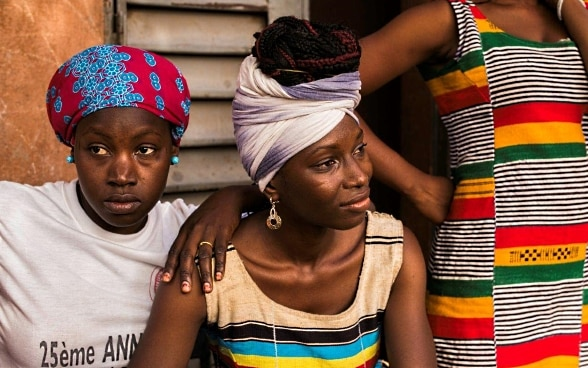 Three young Malian women in brightly coloured clothing looking off into the distance.