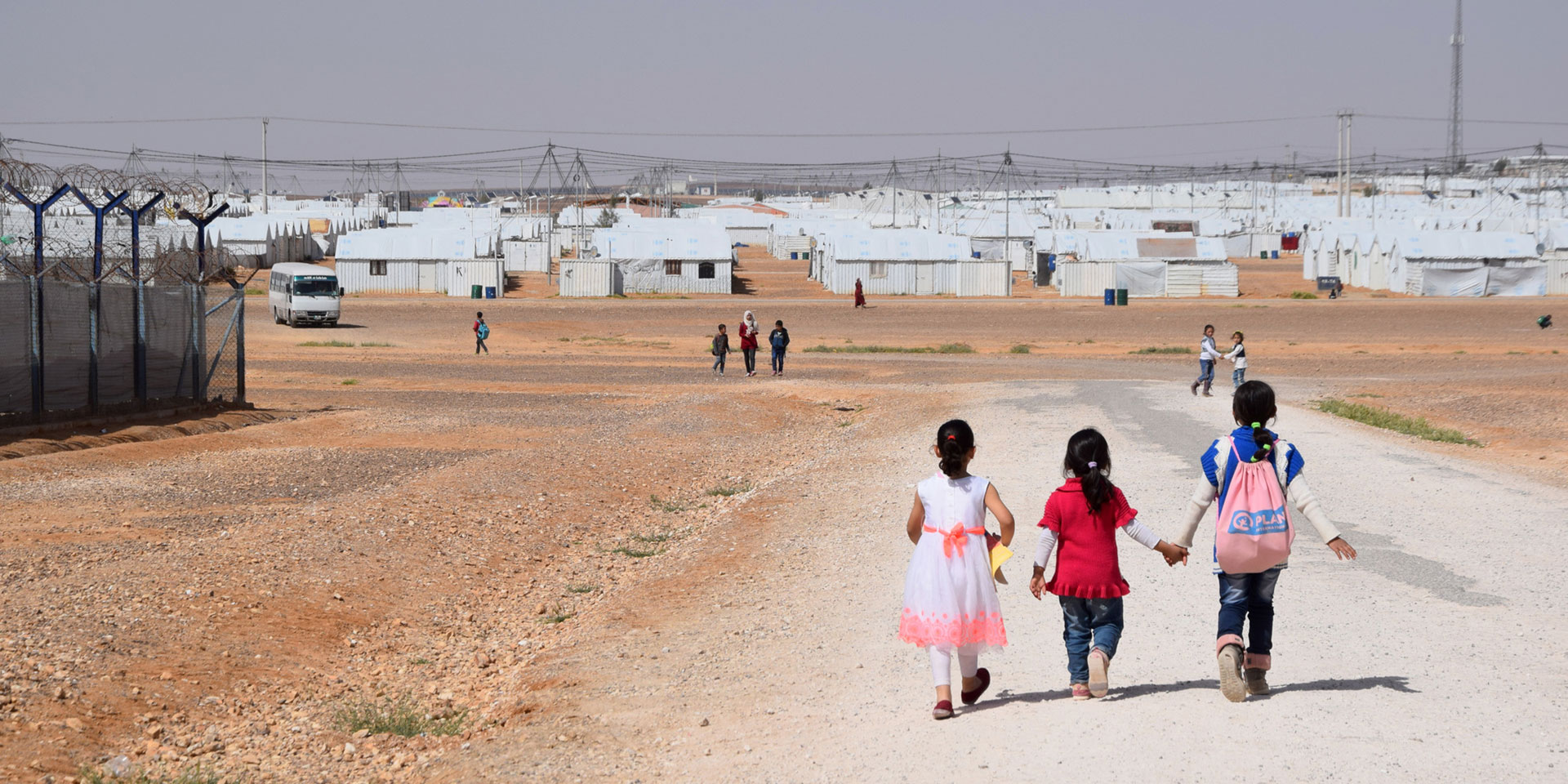 Three girls walk along a gravel path at the Azraq refugee camp in the Jordanian desert.