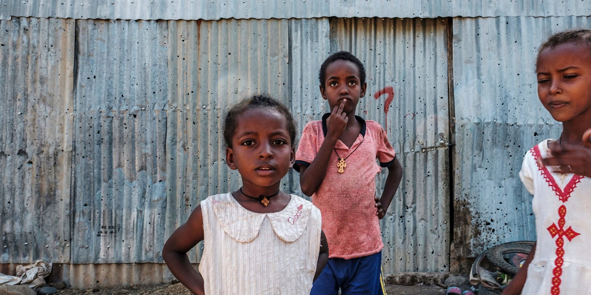Young girls stand in front of a sheet-metal house in Humera, Ethiopia