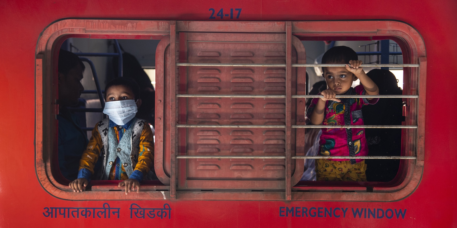 Two children look out of the sliding window of a booth – one with a mask, one without.