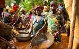 Women, men and children from a village in Sierra Leone, standing waist-deep in water in a gold mine trying to wash away the dirt from the extracted gold.