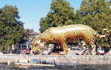On the Île de Rousseau, Geneva, an oversized inflatable jaguar stands at the water's edge.