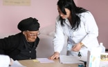 An elderly woman receives prescription in a health care facility in Albania.
