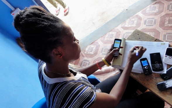 An African woman sits at a table on which several mobile phones are lying and transfers numbers into a table.