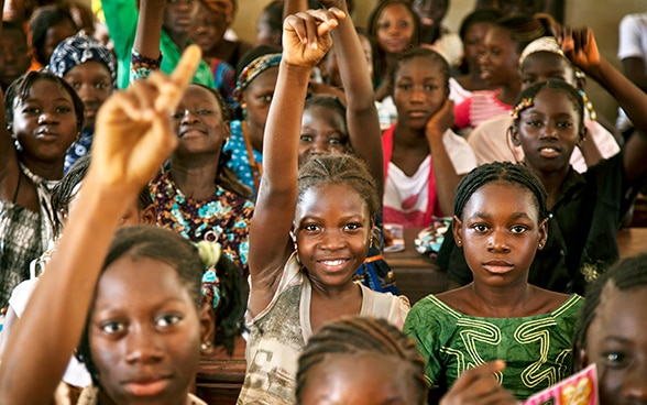 African girls raising their hands.