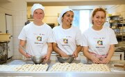 Three young women apprentices working in a bakery.
