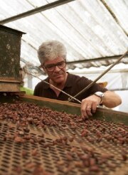Anton von Weissenfluh stands at a conveyor belt transporting cacao beans