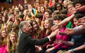 Federal councilor Didier Burkhalter shaking hands with children.