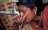 Woman drinks water from a tap.
