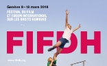 A woman holding onto a man's leg, keeping him from flying away. The FIFDH logo is in the background.