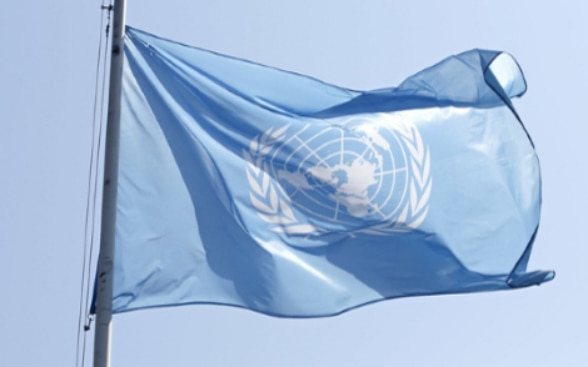 UN flag flying above the Palais des Nations in Geneva.