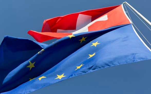 The flags of Switzerland and the European Union flying from one flag pole.