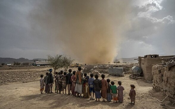 A group of African children watch a sandstorm in an arid sandy environment.