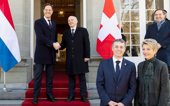 Prime Minister of the Netherlands Mark Rutte (center-left) and Ueli Maurer, President of the Swiss Confederation (center-right) shake hands next to Swiss Federal Councillor Ignazio Cassis (third-right) and Swiss Federal Councillor Karin Keller-Sutter (second-right) prior to their meeting at the Lohn Residence.