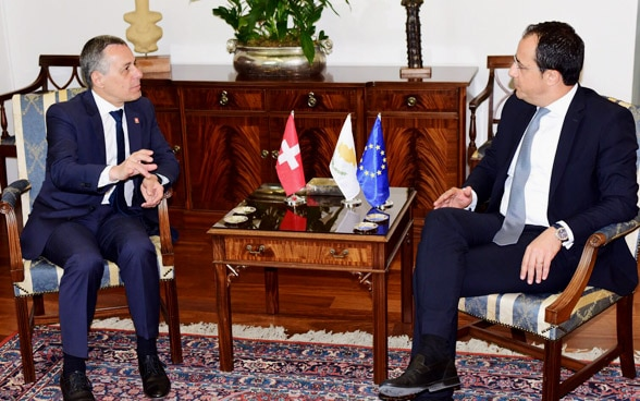 Federal Councillor Cassis and Cypriot Foreign Minister Nikos Christodoulides are sitting at a wooden table and talking