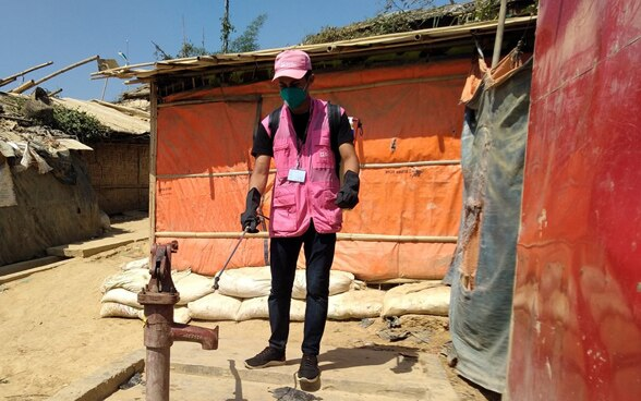 A man in a pink jacket disinfects a well in a refugee camp in Bangladesh.