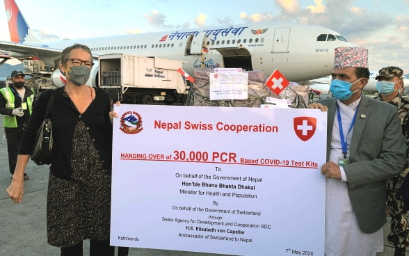 The Swiss ambassador to Nepal and the Nepalese Minister for Health and Population standing in front of an airplane and holding up a poster announcing the handover of 30,000 COVID-19 test kits.