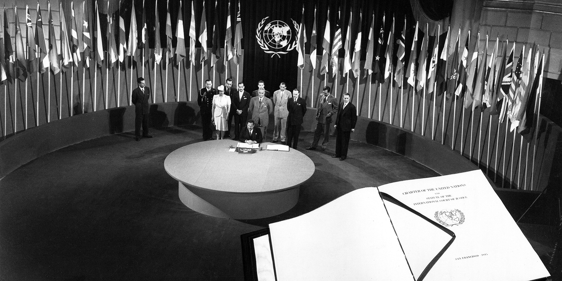 Egypt signing the UN Charter, with the Charter in the foreground.