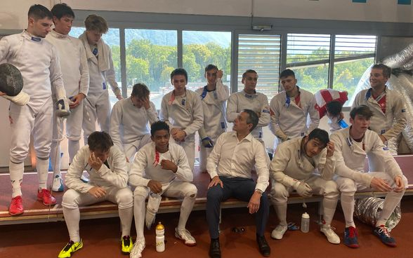 Federal Councillor Ignazio Cassis sits on a bench together with fencers in the school gym.