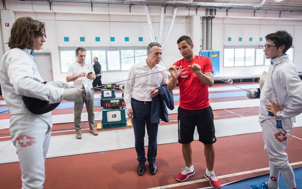 Federal Councillor Ignazio Cassis talks to a fencer in the school gym.