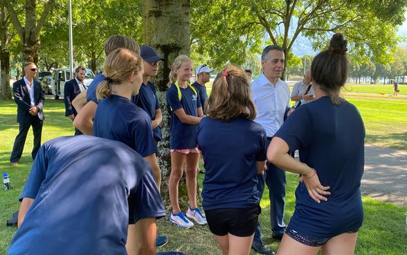 Federal Councillor Ignazio Cassis talks to track and field athletes outdoors.