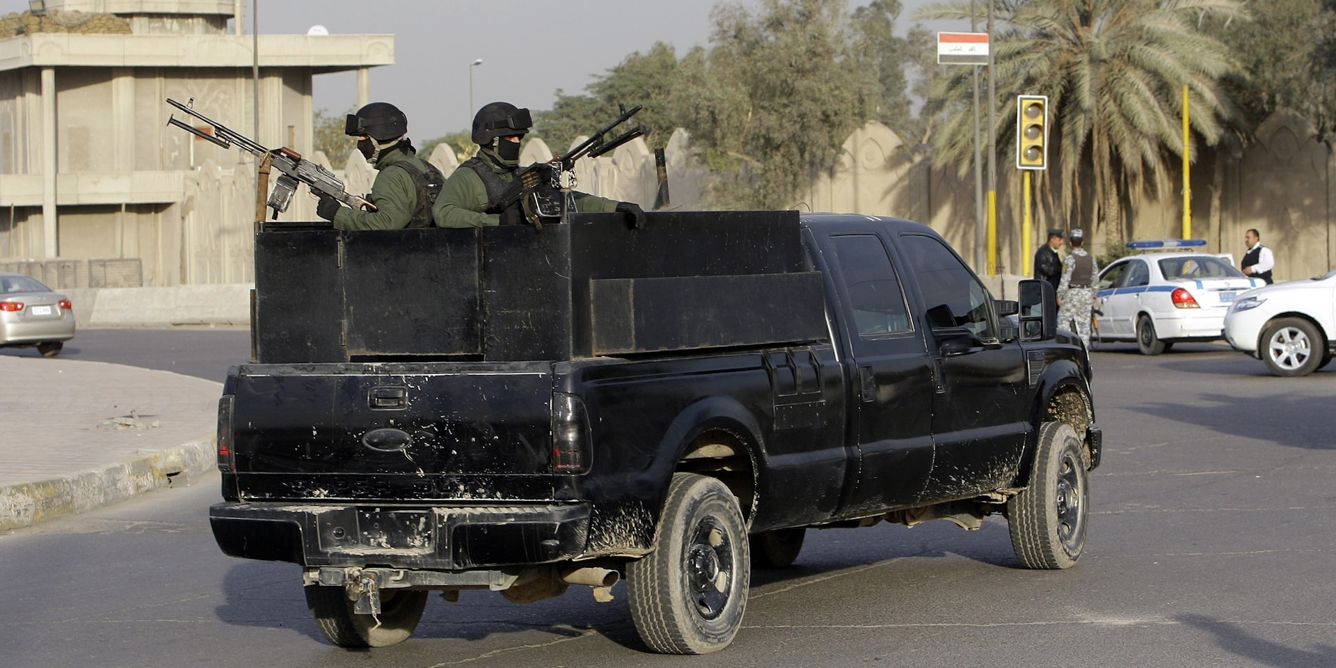 Two masked soldiers from a private security company stand armed to the teeth in the back of a black pick-up truck.