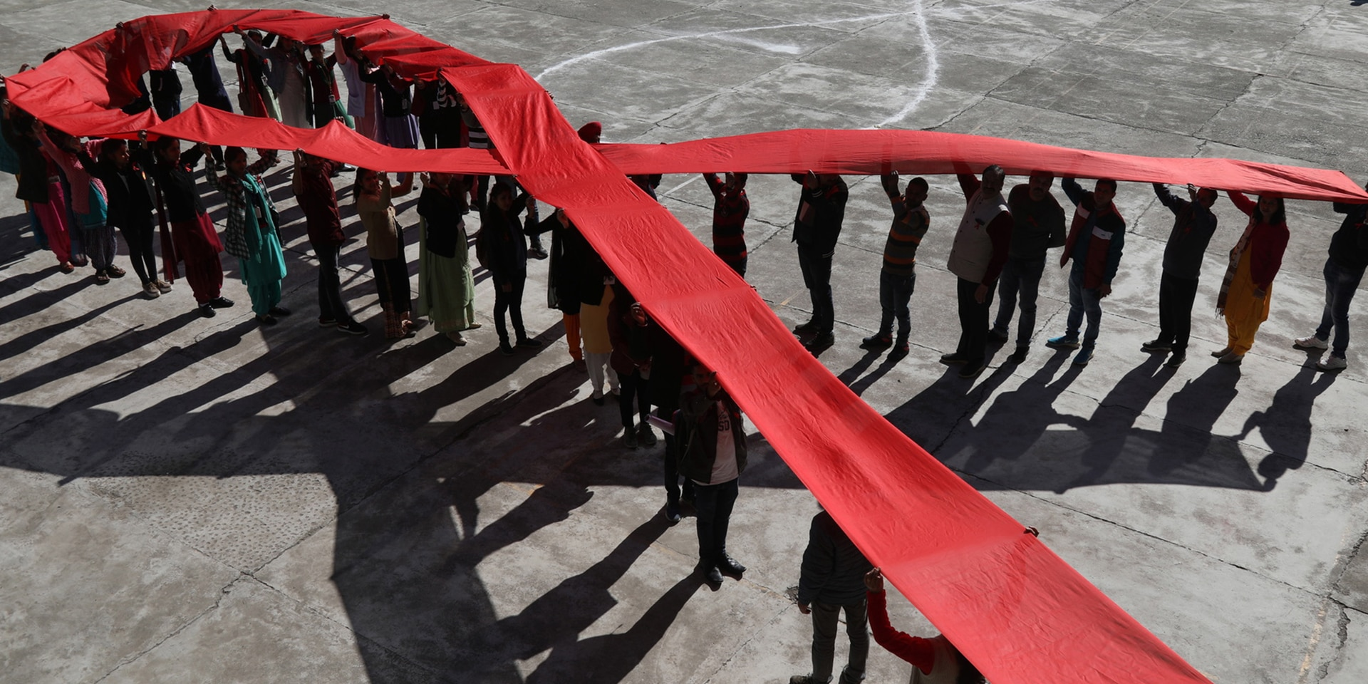 People lined up in the shape of a bow, raising a long red ribbon above their heads to form the internationally recognised symbol of the fight against AIDS.