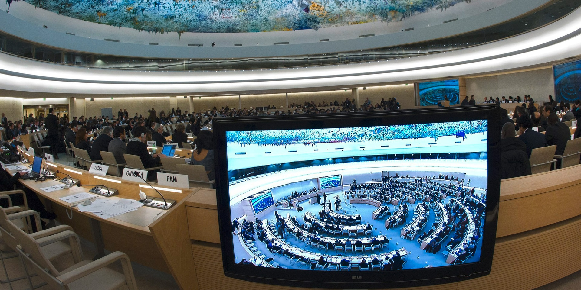 The Human Rights and Alliance of Civilizations Room at the United Nations in Geneva, where the Human Rights Council convenes. In the foreground, a screen showing footage of the conference room.