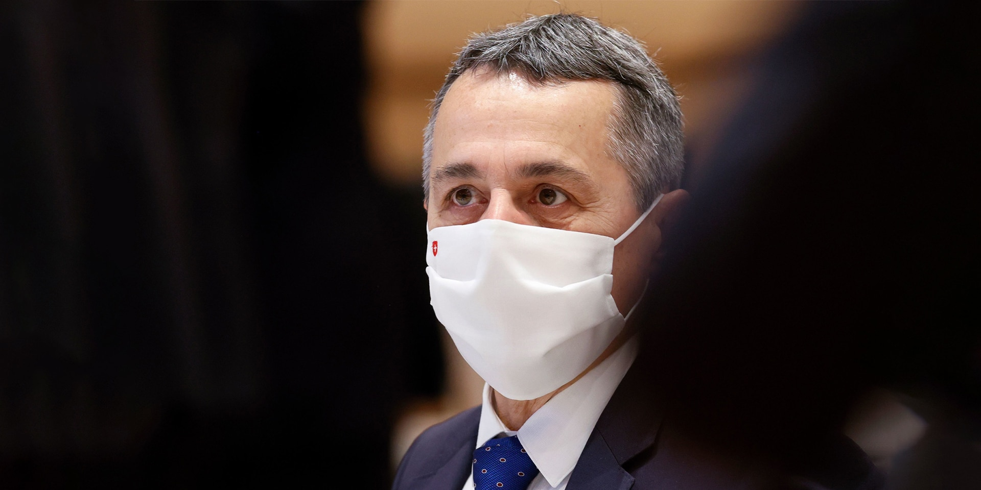 Close-up of Federal Councillor Ignazio Cassis sitting in the room at a UN assembly in November 2020 and wearing a face mask with a Swiss cross.