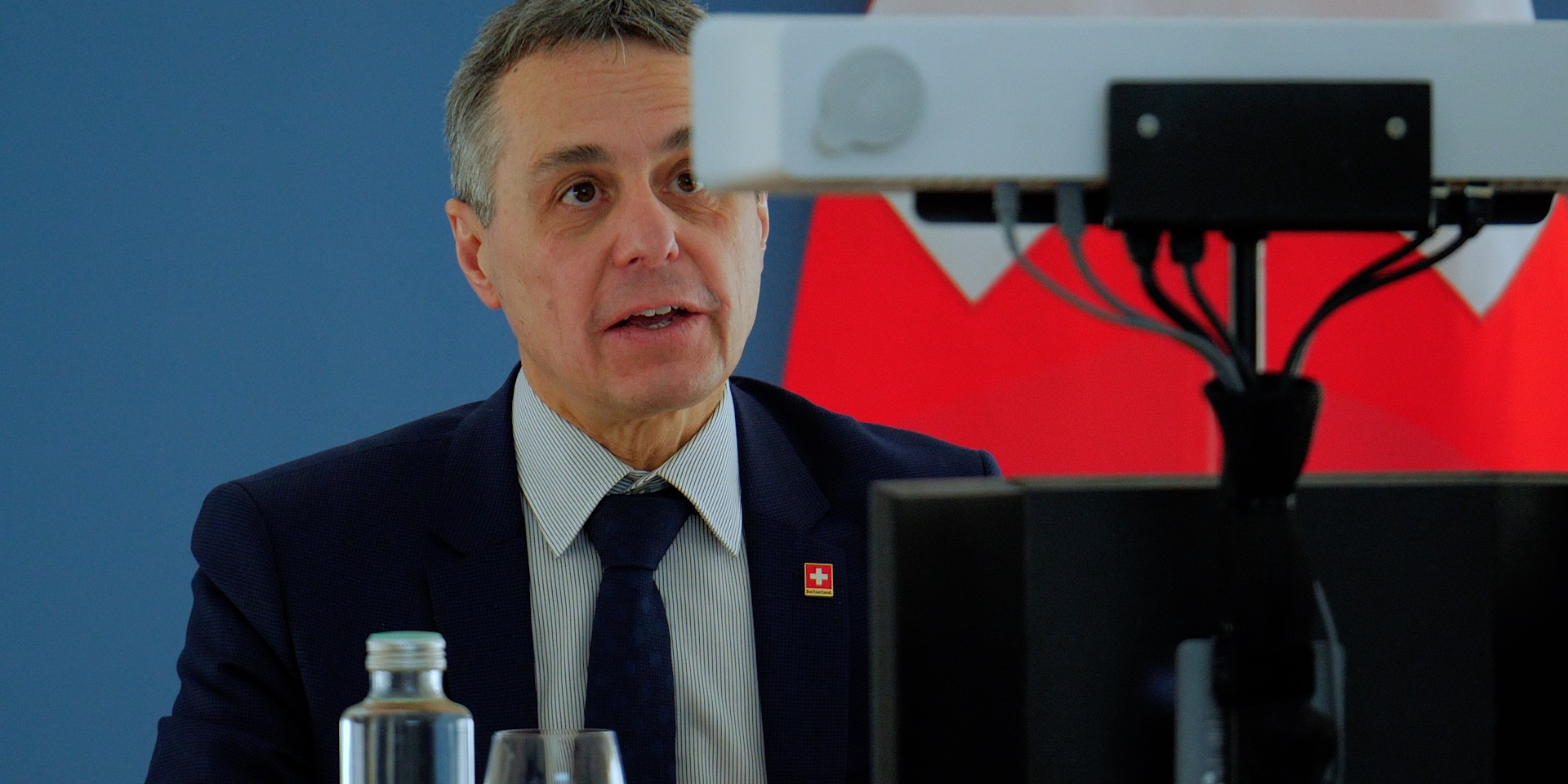 Federal Councillor Ignazio Cassis gives a speech in front of a camera during a virtual conference. Behind him, the Swiss flag.
