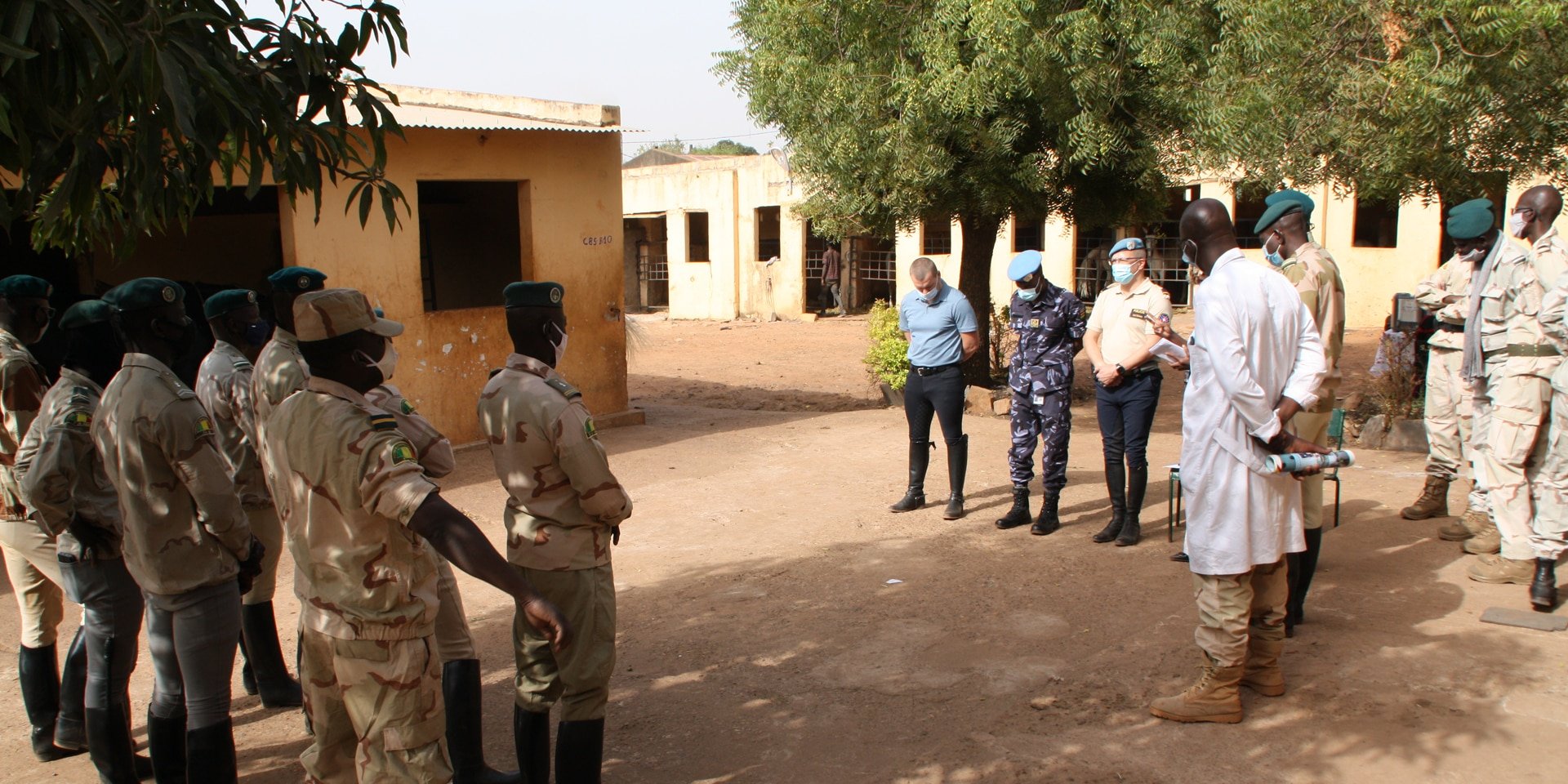 Carl Emery, accompanied by a Malian gendarmerie commander in costume, stands in front of nine uniformed officers.