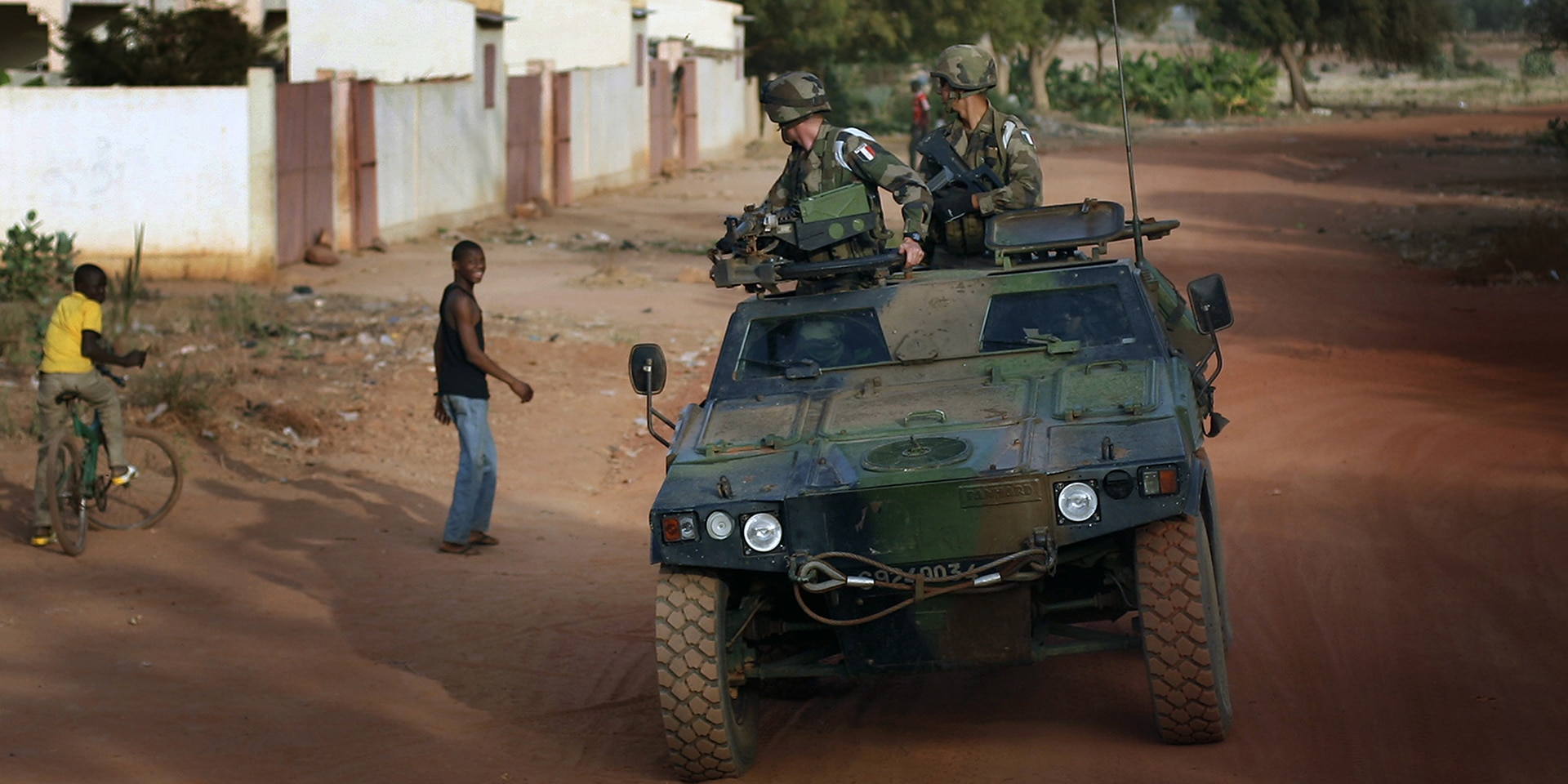 A military vehicle with two soldiers drives past young men in the conflict region of Mali.