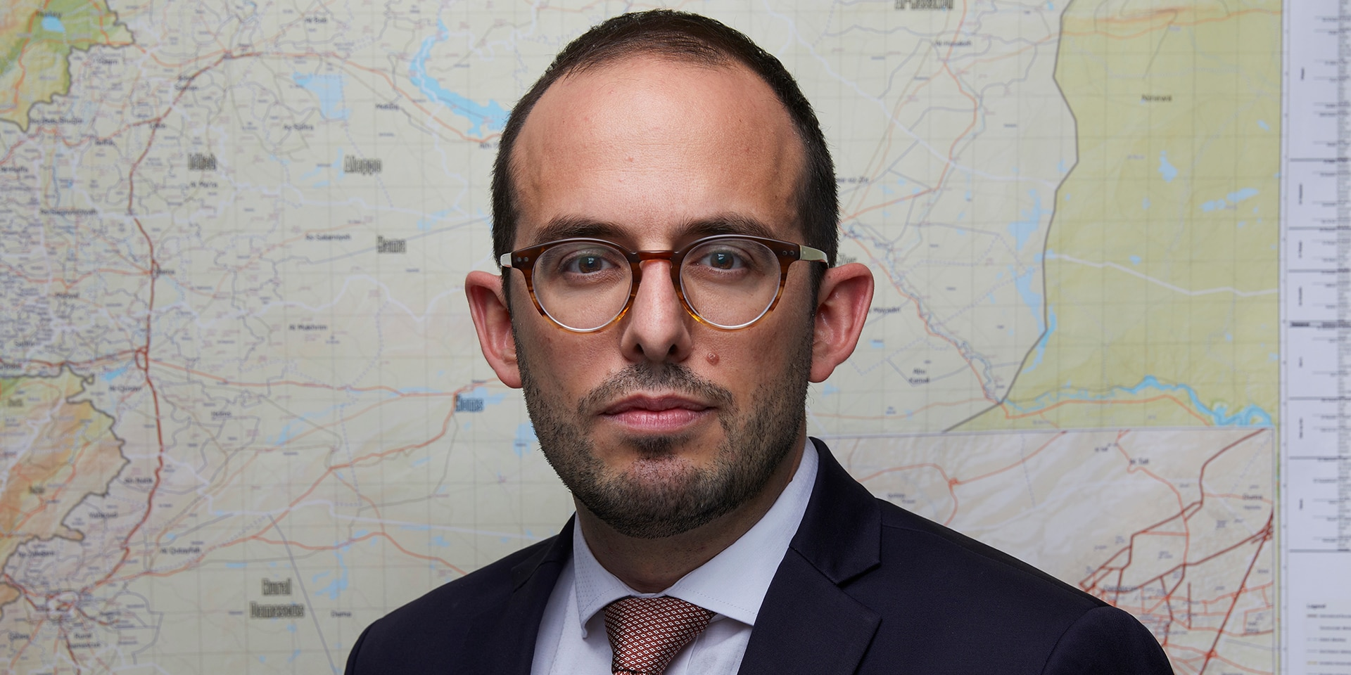 Close-up of Luca Urech in front of a map of Syria.