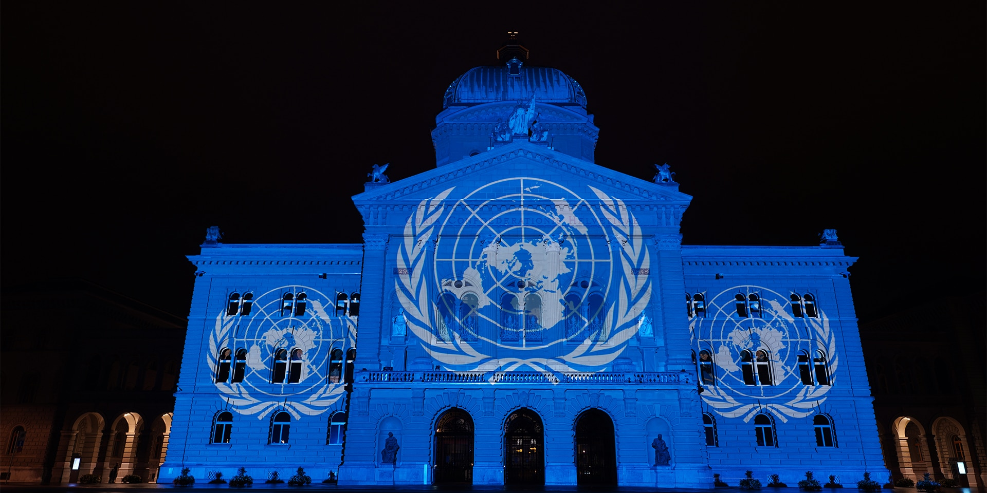 The United Nations flag is projected onto the front of the Federal Palace.