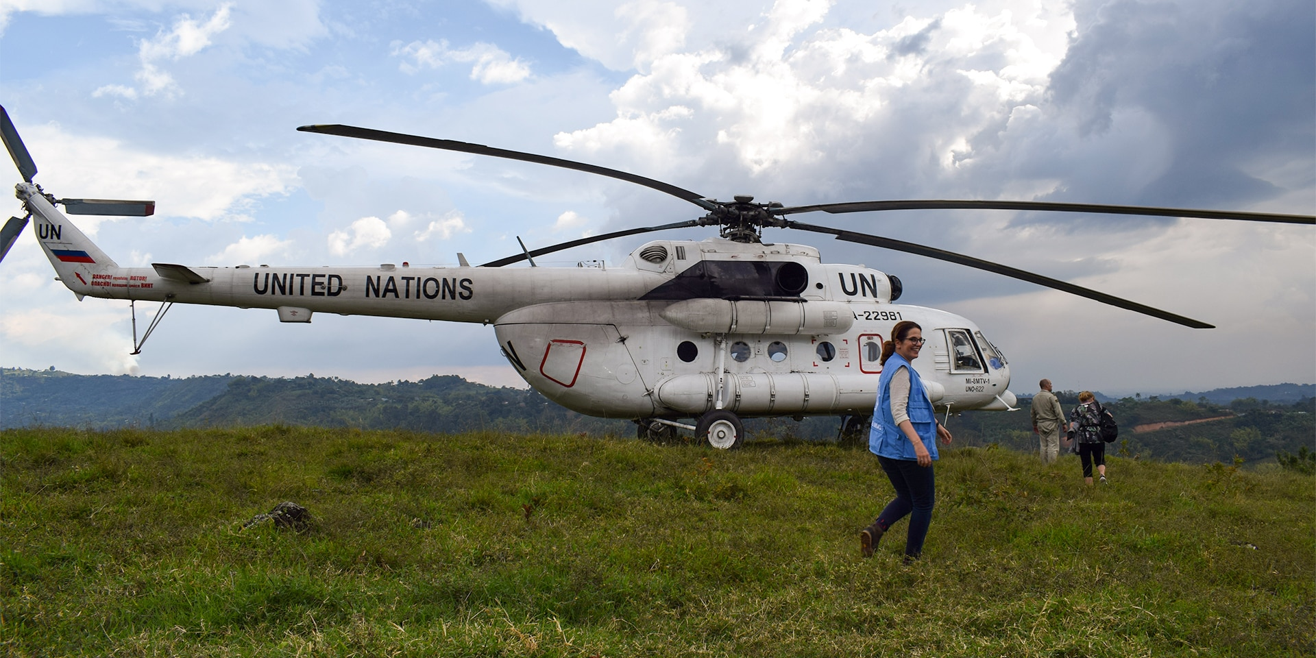 Natalie Kohli in front of a UN helicopter standing on a green lawn.