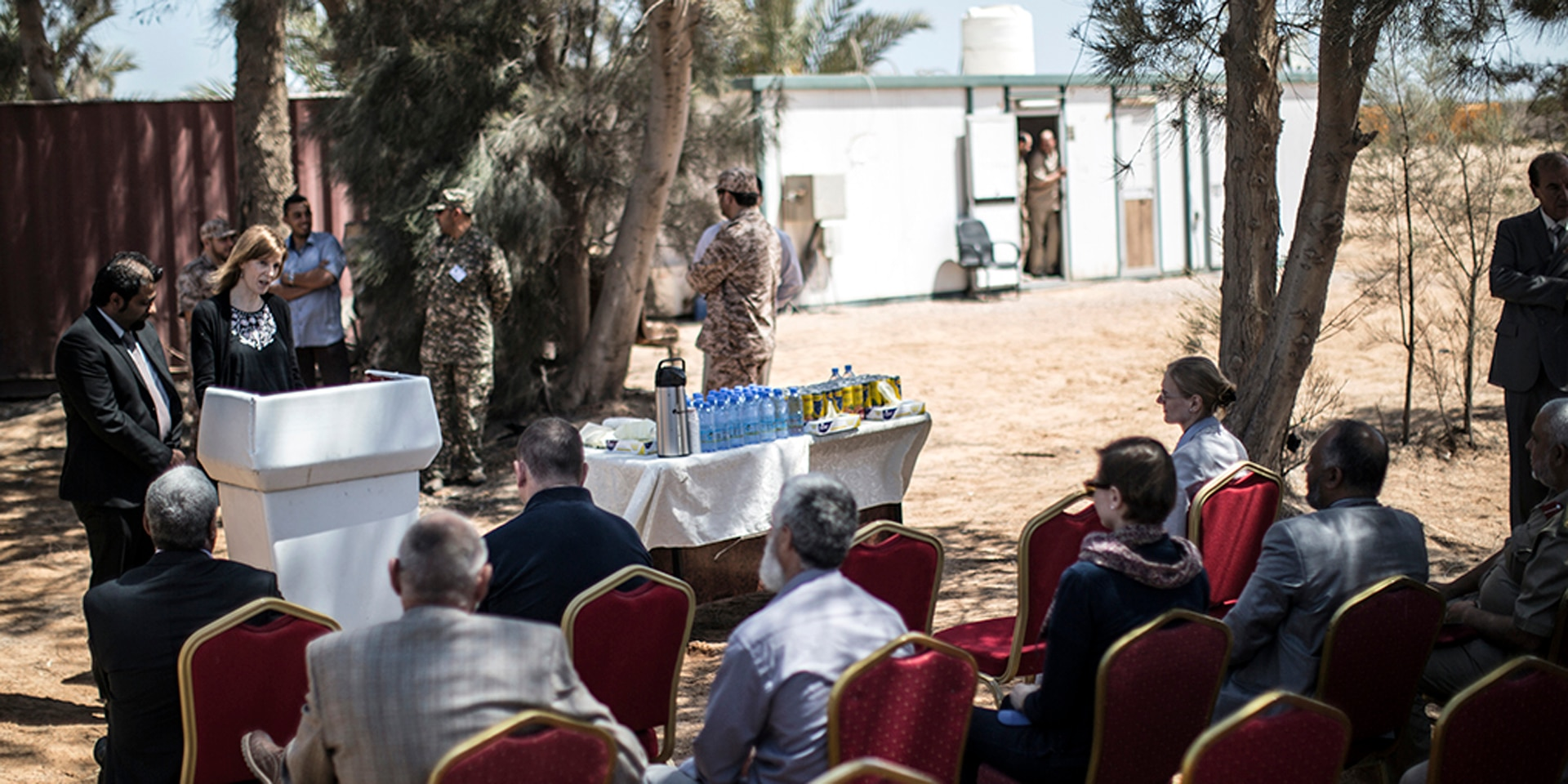 Claudia Marti speaks from a lectern during a conference in Libya.