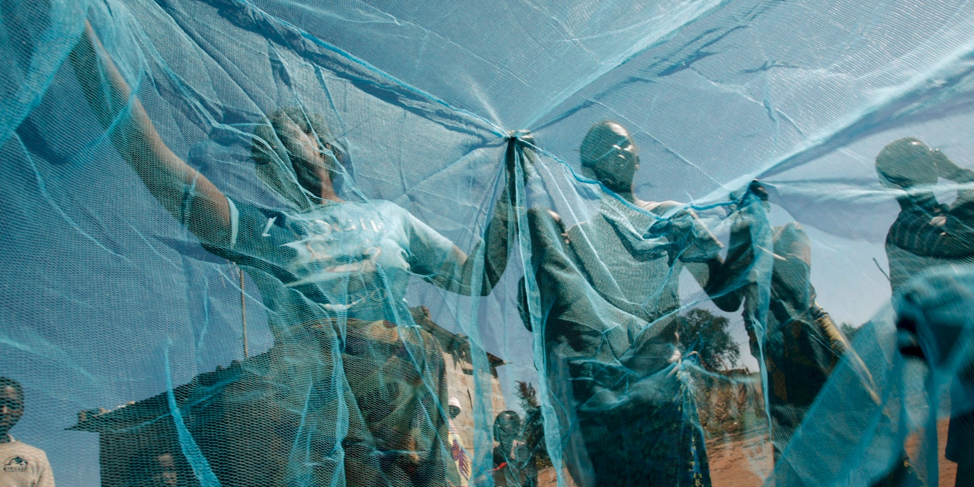 Some children hold up a large blue mosquito net.