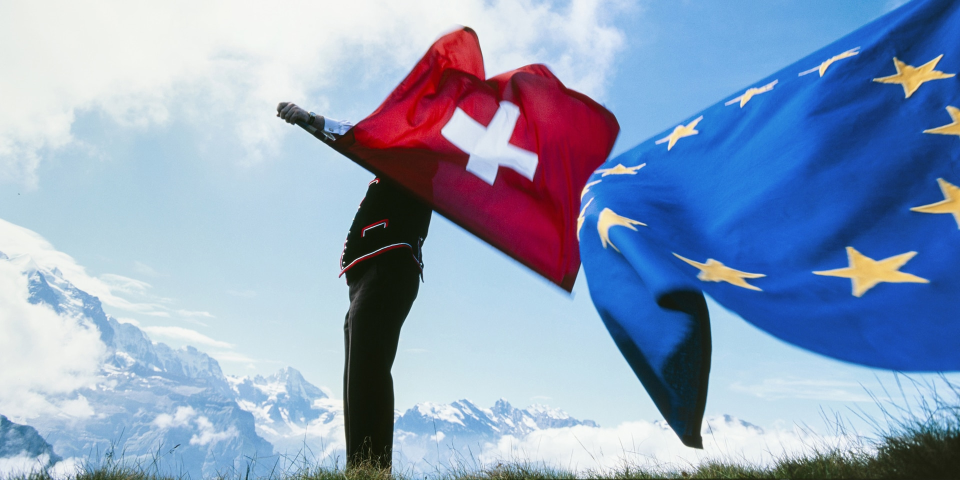 A flag-thrower waving the Swiss flag in one hand and the EU flag in the other against the backdrop of the Bernese Alps.