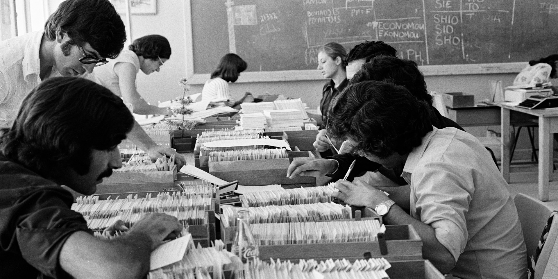 The picture, black and white, shows an office space in 1974. The desks are covered with index boxes filled with index cards. Eight people, concentrated, are working hard.