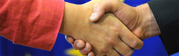 Image of a handshake with European flag in the background