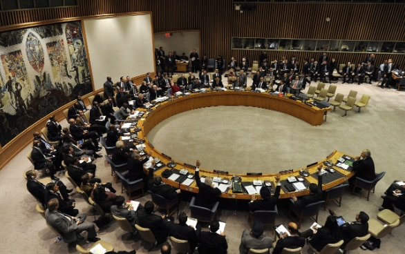 Picture of the UN Security Council: Men and women sitting in a semicircle voting on something.