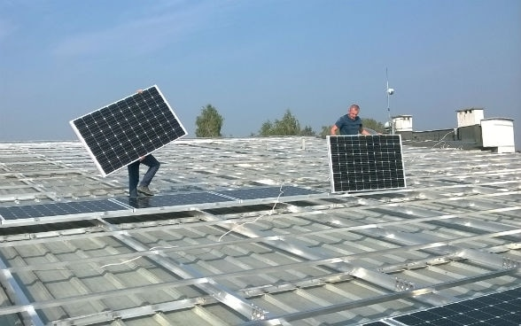 Workers installing solar panels in Niepolomice, Poland.