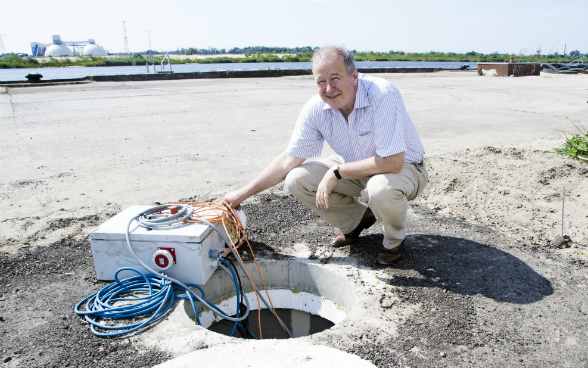 A man sitting in front of a remediation well at an industrial port