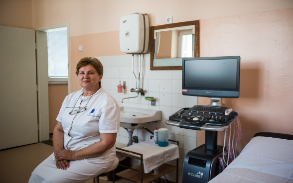 A nurse sitting in a treatment room.