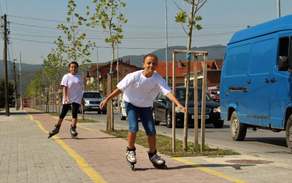 Two young people rollerblading on a cycle path..