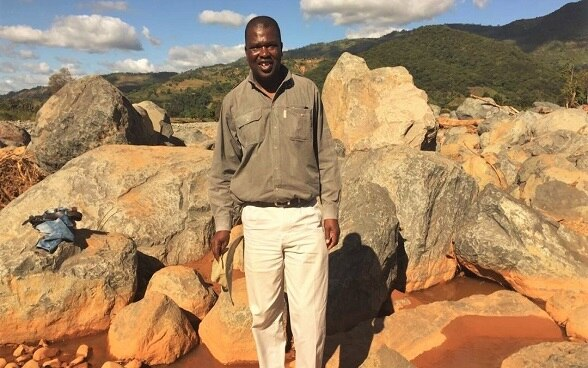 Edson Mugore, Programme Office with the Swiss Agency for Development and Cooperation standing amid the boulders that came on top of houses in Chimanimani in Zimbabwe. Houses and many family possessions were destroyed by Cyclone Idai in March 2019.