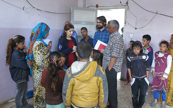 Stefan Bumbacher, accompanied by a WFP colleague, talking with a group of displaced persons.