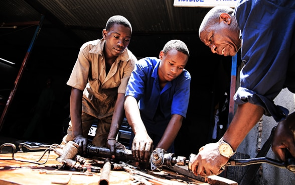 Three men working together on an engine