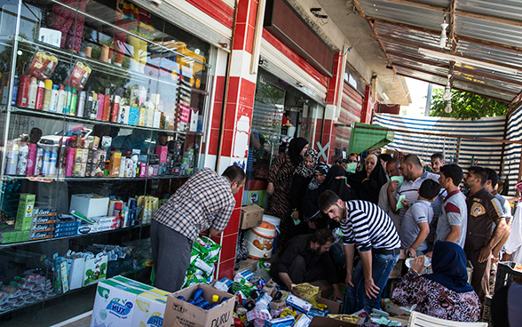 Aid recipients in Iraq queuing outside a supermarket at a point of distribution for food and other goods.