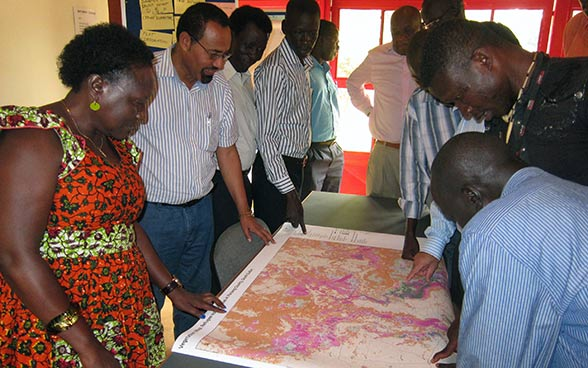 A group of people standing around a table with a map spread over it.
